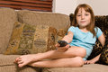 Young female child relaxing watching television sitting corner couch holding t v remote control Royalty Free Stock Photos