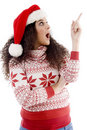 Young female with christmas hat indicating upward Royalty Free Stock Photos