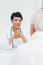 Young female doctor attentively listening to senior patient at the medical office Stock Image