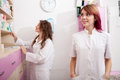 Young female doctor and her assistant working inside a pharmacy Royalty Free Stock Photo