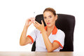 Young female doctor or nurse sitting behind the desk and holding syringe Royalty Free Stock Photo