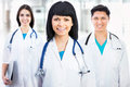 Young female doctor portrait of a standing in front of her team and smiling Stock Photos