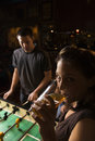 Young female drinking beer at foosball table. Royalty Free Stock Photos