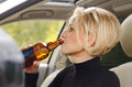 Young female driver drinking bear in the car blond woman alcohol from bottle and driving with smile of enjoyment on her face as Stock Image