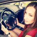Woman using smartphone driving the car