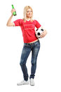 Young female fan holding a beer bottle and football full length portrait isolated on white background Stock Photos