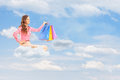 Young female flying on cloud and holding bags against cloudy sky shopping Royalty Free Stock Photo