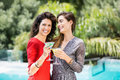 Young female friends drinking cocktail by during party cheerful swimming pool Stock Image
