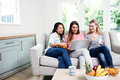 Young female friends looking in laptop at home while sitting on sofa Royalty Free Stock Photos