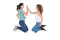 Young female friends playing clapping game side view of happy over white background Stock Image