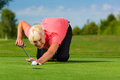 Young female golf player on course aiming for put her Stock Image