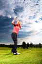 Young female golf player course doing golf swing presumably does exercise Royalty Free Stock Image