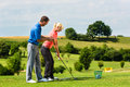 Young female golf player on course at driving range with a pro she presumably does exercise Stock Images