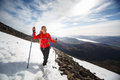 Young female hiker going uphill crossing a snow field pretty Stock Photos