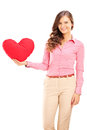 Young female holding a red heart shaped pillow and smiling isolated on white background Royalty Free Stock Photography