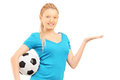 Young female holding a soccer ball and gesturing isolated on white background Royalty Free Stock Photo
