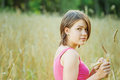 Young female holding spica cute stands in crop field Stock Photos