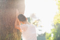 Young female lean against tree. Rear view Royalty Free Stock Images