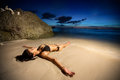 Young female model lying in water on golden sunset Royalty Free Stock Photo