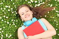 Young female with notebook listening music and lying on a grass daisies Royalty Free Stock Photography