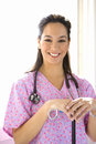 Young female nurse with stethoscope, smiling, portrait Royalty Free Stock Photo
