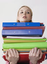 Young female office worker carrying heavy binders against gray background Stock Photography