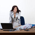 Young female office worker standing behind a desk with a stern look Royalty Free Stock Photos