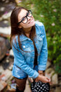 Young female outdoors happy in jeans wear smiling wearing glasses and hat view from above Royalty Free Stock Photo