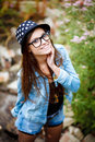Young female outdoors portrait of happy in casual wear smiling wearing glasses and hat view from above Stock Image