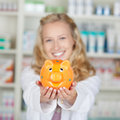 Young female pharmacist holding piggybank portrait of in pharmacy Stock Image
