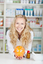 Young female pharmacist with piggy bank portrait of in pharmacy Stock Images