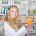 Young female pharmacist smiling with piggy bank portrait of in pharmacy Royalty Free Stock Image