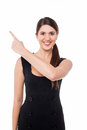 Young female pointing away smiling beautiful woman against white Stock Images