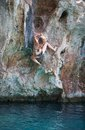 Young female rock climber on face of cliff deep water soloing Stock Image