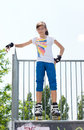 Young female roller skater attractive teenage posing at the top of a cement ramp in her rollerblades looking down at the camera Stock Photos