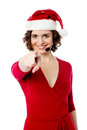 Young female santa pointing towards you smiling the camera Royalty Free Stock Photography