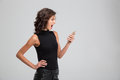 Young female screaming and using mobile phone mad angry Royalty Free Stock Photo