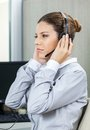 Young female service agent listening to customer wearing headset and carefully in office Royalty Free Stock Image