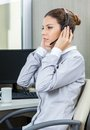 Young female service agent listening to customer wearing headset and carefully in office Royalty Free Stock Photography
