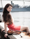 Young female sitting on a pier pretty with violin Royalty Free Stock Photography