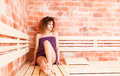 Young female sitting on wood bench in sauna Royalty Free Stock Photo