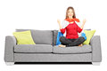Young female sport supporter sitting on a modern sofa and cheeri cheering isolated white background Stock Photo
