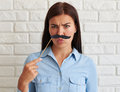 Young female standing and frowning her brows astonished in casual wear holding a black moustache on stick Royalty Free Stock Image
