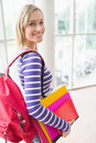 Young female student with backpack and books Royalty Free Stock Photo