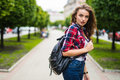 Young female student with backpack walking in the park Royalty Free Stock Photo