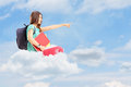Young female student with bag pointing with her finger and sitti school sitting on a cloud Stock Photography