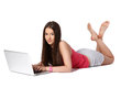 Young female student casually lying on the floor with a laptop Royalty Free Stock Image