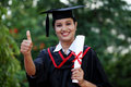 Young female student with diploma at outdoors and making thumbsup Stock Images