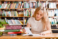 Young female student doing assignments in library Royalty Free Stock Photo