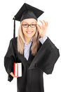 Young female student in graduation gown holding books Stock Images